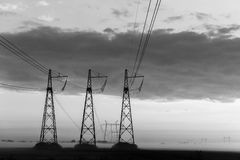 Reliance power lines. Black-white photo. Reliance power lines on background of cloudy sky evening black and white photo Royalty Free Stock Photography