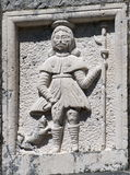 Relief of knight. Old relief of knight with animal at his feet Royalty Free Stock Photography