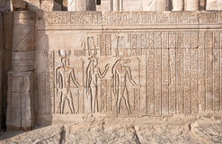 Relief from Kom Ombo, Egypt. Relief of Khonsu, god of the moon, Hathor his mother, goddess of love and pleasure, and Sobek his father, god of power and strength Royalty Free Stock Photo