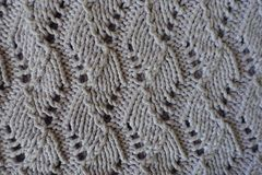 Relief pattern with perforations on handmade gray knitwork. Relief pattern with perforations on hand made gray knitwork Stock Photos