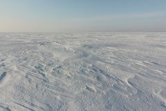 Relief snowy surface of the frozen river at dawn. Ob River, Siberia, Russia royalty free stock photo