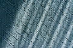 Pleasing texture detail of scratched stucco plaster. Interior close-up. Blue embossed wall lit by sunlight. Playful diagonal shadows. Abstract optimistic retro royalty free stock image