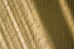 Texture from embossed stucco plaster lit by sunlight with playful shadows. Close-up of beige wall in retro style with pattern from diagonal scratches. Pleasing stock photos