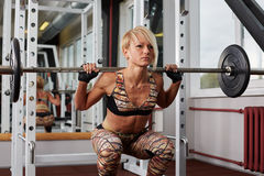 Reliefed athlete blonde woman making squats in power rack Stock Photo