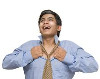 Relieved businessman breathing. Young Indian or Asian corporate businessman cheering, smiling and opening his collar and necktie, breathing free and liberated Stock Photos