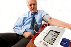 Relieved senior man with low blood pressure. Relieved senior man in blue shirt and tie (businessman or teacher) with a low blood pressure reading on the monitor Stock Photos