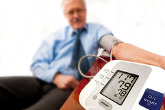Relieved senior man with low blood pressure. Relieved senior man in blue shirt and tie (businessman or teacher) with a low blood pressure reading on the monitor Royalty Free Stock Photos