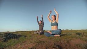 Religi?n de la yoga, par de los deportes junto que medita en la posici?n de loto respecto a prado en el fondo del cielo almacen de video