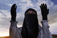 Religiös asiatisk muslimkvinna med hijab som lyfter handen och att be Arkivbilder