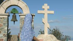 Religiös kvinna som ser stenkorset med hopp Symbol av kyrkan, religion lager videofilmer