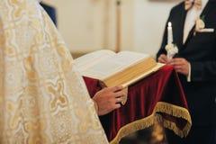Religiös man som läser den heliga bibeln och ber i kyrkan med tänt stearinljus-, religion- och trobegrepp arkivbilder