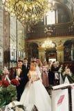 Religiöse blonde Braut und hübscher Bräutigam in den Kronen in der Kirche an Lizenzfreie Stockfotos