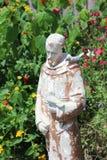 Religiöse Figur in einem Garten Stockfotografie