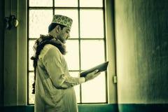 Religiöse moslemische Mannstellung und Lesungsheiliges koran innerhalb MOS Stockfotos
