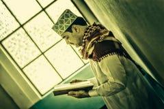Religiöse moslemische Mannstellung und Lesungsheiliges koran innerhalb MOS Lizenzfreies Stockfoto