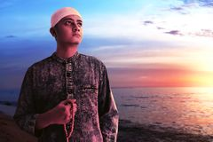 Religi?s asiatisk muslim man med radbandp?rlor arkivfoton