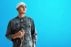 Religi?s asiatisk muslim man med radbandp?rlor arkivbilder