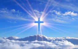 Religieux croisez au-dessus des cumulus illuminés par les rayons du rayonnement saint, concept photographie stock