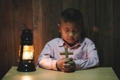 Religijna Chrześcijańska chłopiec ono modli się nad biblią indoors obraz royalty free