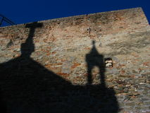 Religion. Shadow of a church against an old stone wall in italy Stock Photography