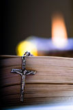 Religion. Old Cross and the Holy Bible laying on the table in fornt of a lighting candle Royalty Free Stock Photos