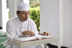 Religion asian muslim man with cap reading holy book Koran Royalty Free Stock Image