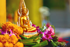 Religion. Buddha Statue With Flowers At Temple, Thailand. Buddhi. Religion. Close Up Of Small Golden Buddha Statue In Lotus Position With Flowers At Wat Phra Yai Stock Photo
