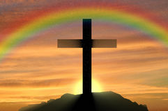 Religion Christianity. Cross silhouette. Against the sunset and the rainbow Royalty Free Stock Photos