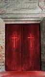 Religion concept - cross on door. Cross on spooky red church door. Worship concept Royalty Free Stock Photography