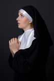 Religion concept - young woman nun praying over grey Royalty Free Stock Images
