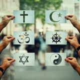 Religion conflicts global issue. Religion conflicts as global issue concept. Human hands holding different paper with faith symbols over crowded street scene royalty free stock images