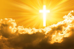 Christian Cross Sky God Background. A glowing cross in a golden sunlit sky background Stock Images