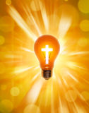 Religion Cross Light Bulb Christianity. A light bulb and cross with a shaft of light in the background Stock Images