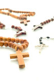 Religion diversity - rosary beads over white. With focus on one cross (shallow DOF Royalty Free Stock Image