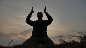 religion f?r bokbegreppskors Kontur av en manlig munk som ?r f?rlovad i meditation p? solnedg?ngsolljus Buddistisk bön på den sun lager videofilmer