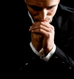 Religion and faith - prayer of man. Low-key portrait of businessman praying for success Royalty Free Stock Photos