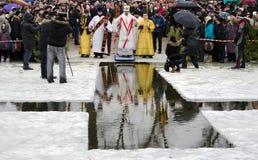 Religion, festin de l'épiphanie. Le prêtre bénit l'hiver l'eau en rivière, dans le trou Photos stock