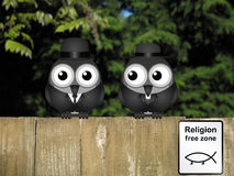 Religion Free Zone. Comical bird vicar and businessman with evolution religion free zone sign perched on a timber garden fence against a foliage background vector illustration