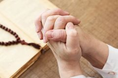 Religion. Hands of prayer with bible on the background. Close-up Royalty Free Stock Photos