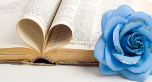 Religion Love. A couple of bible pages folded to make a heart with a artificial flower on the side Stock Photography
