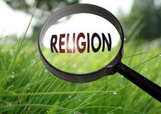 Religion. Magnifying glass with the word religion on grass background. Selective focus Royalty Free Stock Photography