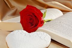 Religion and purity, symbols. A red rose on an opened Bible, next to a white heart shaped object suggesting the blood of Jesus and the purity of love Stock Photography