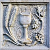 Religion scene with chalice. Grain and grapes in stone Royalty Free Stock Images
