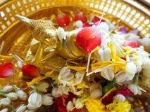 Religion Slut upp av den lilla guld- Buddhastatyn med blommor Royaltyfria Bilder