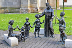 Religion Statuary. Religion concept with a priest taking care of children Stock Photo