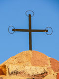 Religion symbols. Christian cross. Simple iron cross on the belfry of the medieval rural church of Santa Marta, in south-west Sardinia Stock Photos