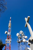 Religion and technology. Cross monument near radio tv and telephone repeater Stock Photo