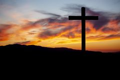 Religion theme, catholic cross and sunset. Religion theme, view of catholic cross in black shadow, with fantastic sunset with warm colors and mountains as royalty free stock photo