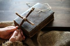 Religion tom book cross burlap. Ancient religious book and wooden cross on the background of a wooden and burlapr Stock Image