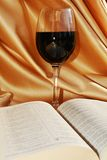 Religion and wine, symbols. A glass of red wine next to an opened Bible, suggesting the blood of Jesus, the sacrifice and the love for mankind Royalty Free Stock Images